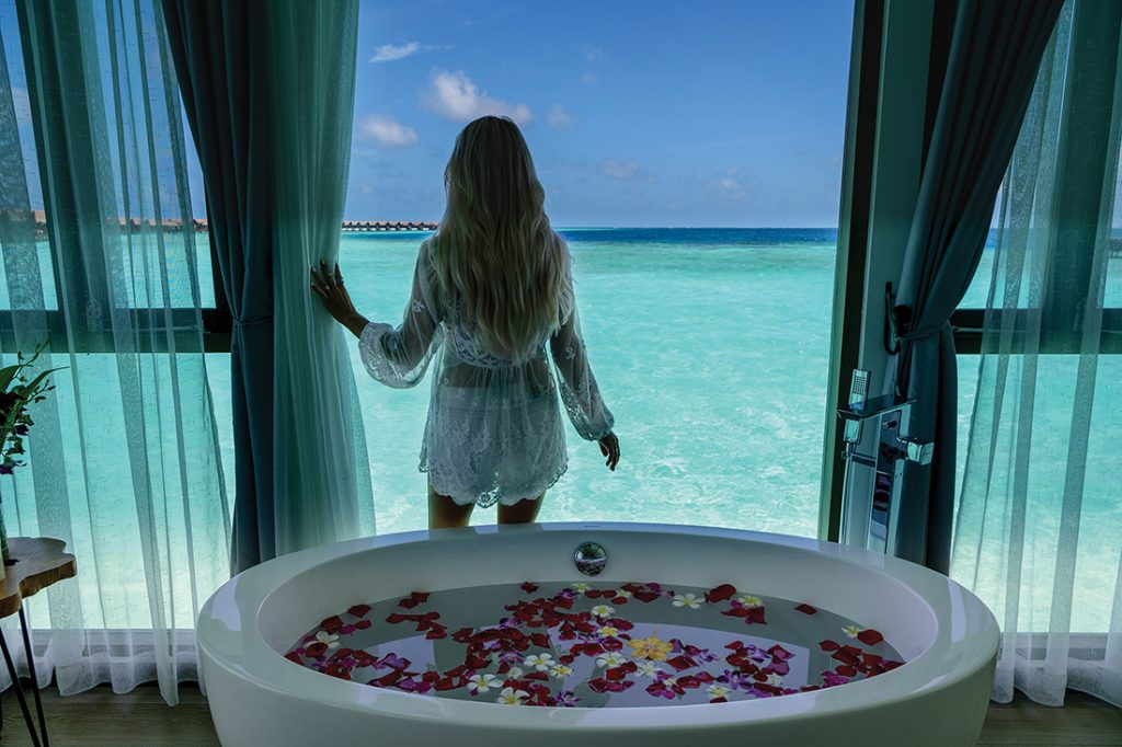Woman looking out spa window onto sea at Grand Park Kodhipparu, Maldives