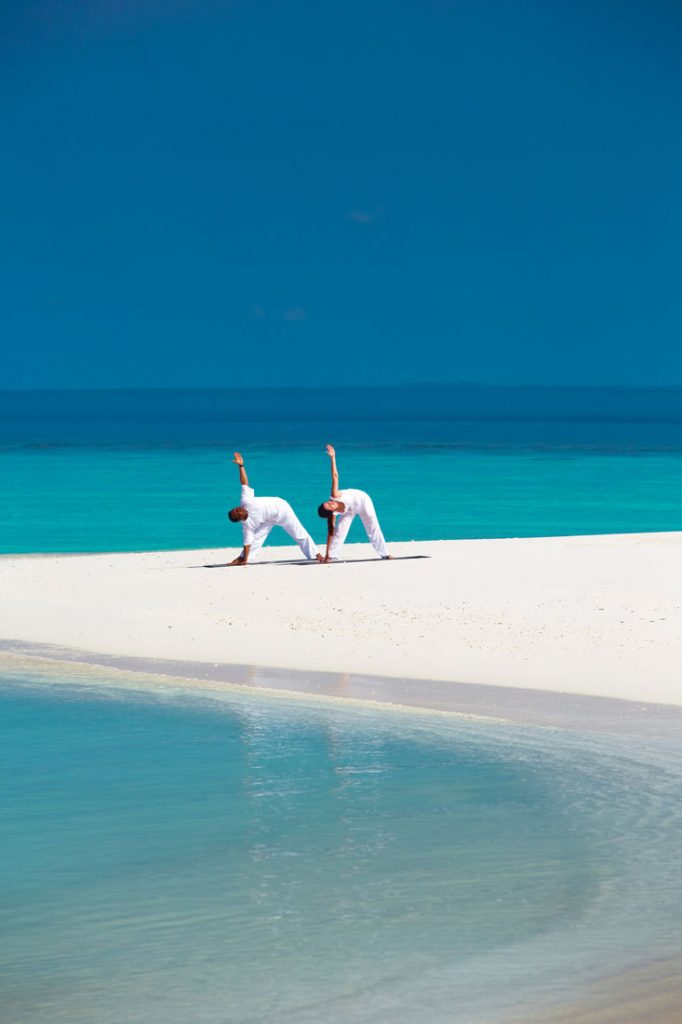 two people doing yoga on the beach at Anantara Kihavah Maldives Villas