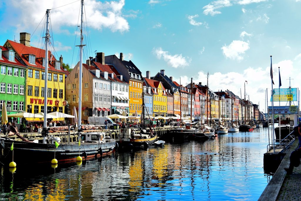 Colourful buildings overlooking boats at Nyhavn District canal in Copenhagen, Denmark