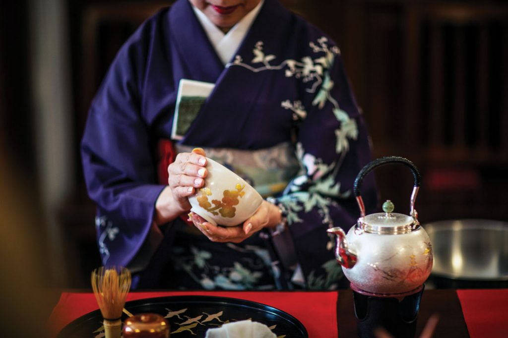 woman holding traditional Japanese tea cup in ceremony