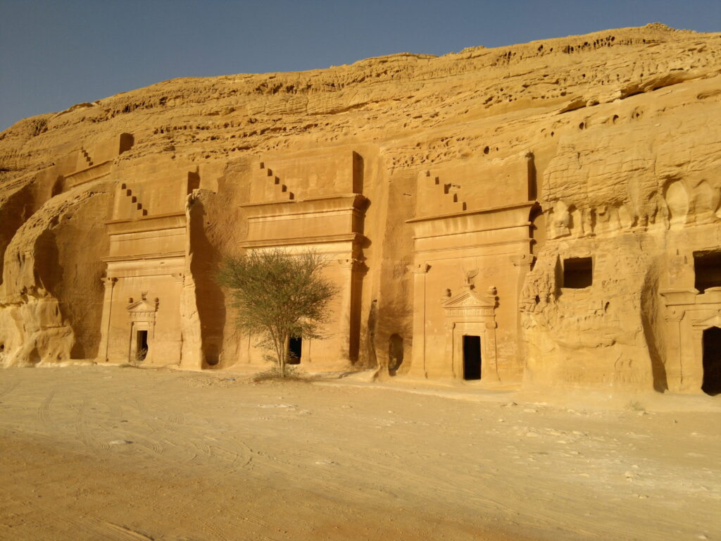 Sand -coloured tombs carved into a cliff wall the Al Ula ruins of Saudi Arabia