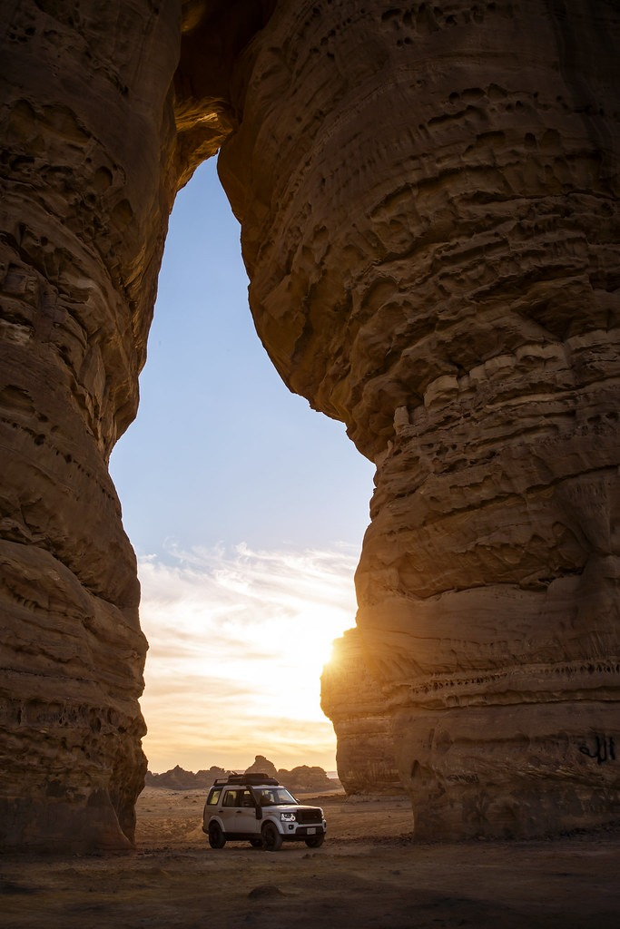 Car parked in an opening in the red stone Tabuk valleys, Saudi Arabia at sunset