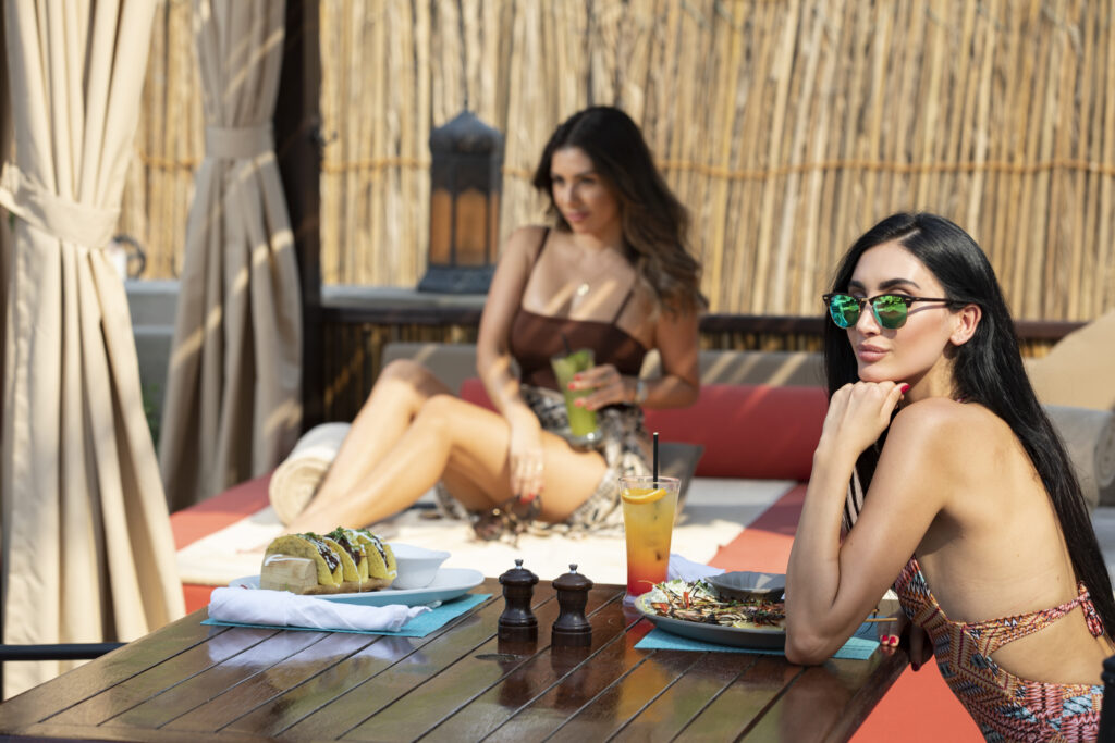 Two women sat in a private cabana experience