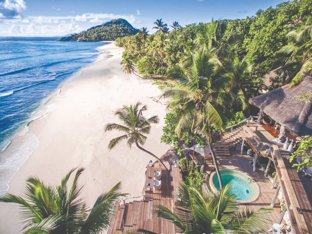 Palm trees and sandy beach at North Island, Seychelles