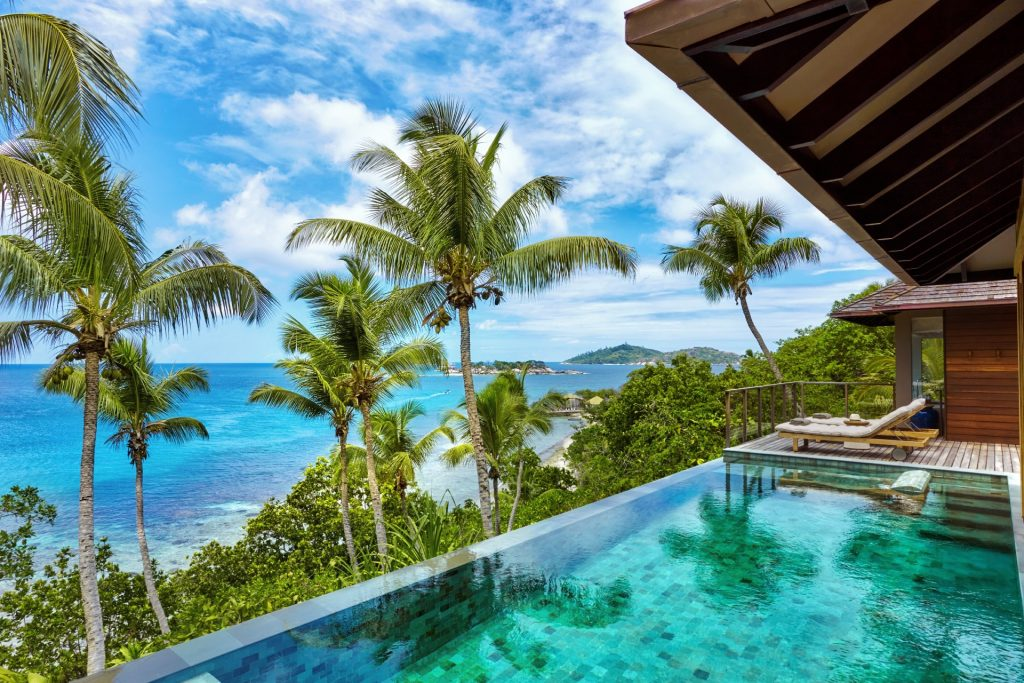 Infinity pool overlooking sea with palm trees surrounding at Six Senses Seychelles