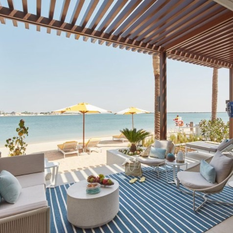 Outdoor chairs and tables under terrace overlooking beach and sea at Vida Beach Resort in Umm Al Quwain
