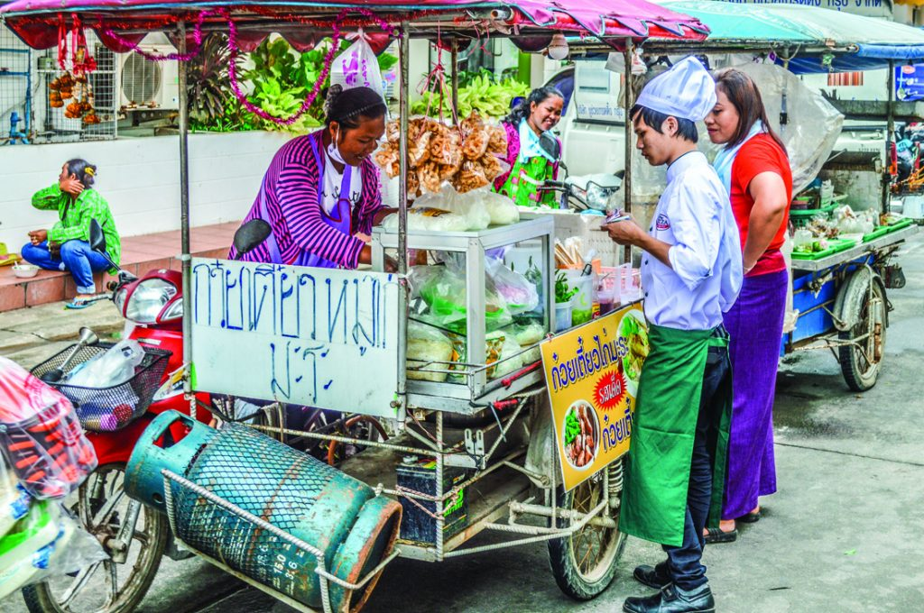 A street food vendor in Phucket prepares meals for customers while shoppers eager wait in line for a delicious meal.